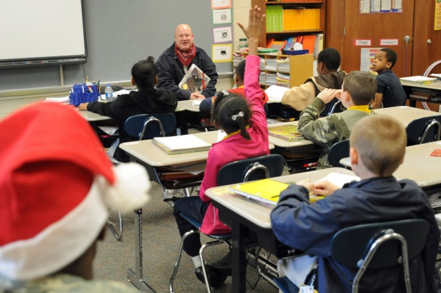 Sgt. 1st Class Charles C. Harris, a maintenance supervisor with Company B, 703rd Brigade Support Battalion, 4th Infantry Brigade Combat Team, 3rd Infantry Division, answers a student's question, Dec. 14, 2011, during a holiday reading program at Liberty Elementary, in Midway, Ga.