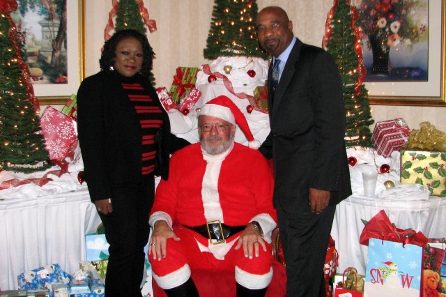 Santa delivers gifts from the FORSCOM logistics directorate to more than 50 needy children to social worker Sandra Robinson and child protection investigator Melvin Roach of the Cumberland County (N.C.) Department of Social Services.