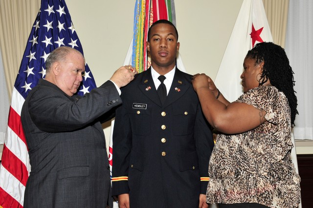 Under Secretary of the Army Joseph W. Westphal pins second lieutenant rank on newly commissioned 2nd Lt. Marcus A. Hemsley, with his mother, during the University of Maryland's Fall Commissioning Ceremony in the Pentagon's Patriot Room. Two other University of Maryland Reserve Officer Training Corps cadets were commissioned into the United States Army as second lieutenants. Their commissioning signifies the completion of a rigorous four-year program.