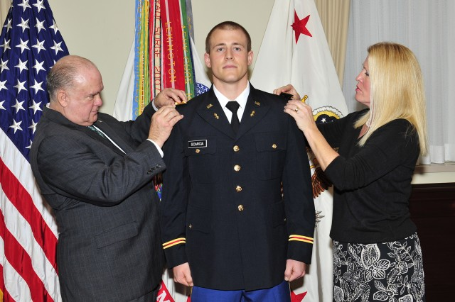 Under Secretary of the Army Joseph W. Westphal pins second lieutenant rank on newly commissioned 2nd Lt. Ross Scarcia, with his mother, during the University of Maryland's Fall Commissioning Ceremony in the Pentagon's Patriot Room. Two other University of Maryland Reserve Officer Training Corps cadets were commissioned into the United States Army as second lieutenants. Their commissioning signifies the completion of a rigorous four-year program.