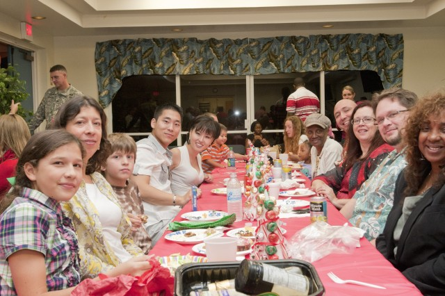 Soldiers and family of the 94th Army Air and Missile Defense Command enjoy their holiday party over a pot luck dinner. (Photo by SFC Adam Phelps 120911-A-ID360-001)