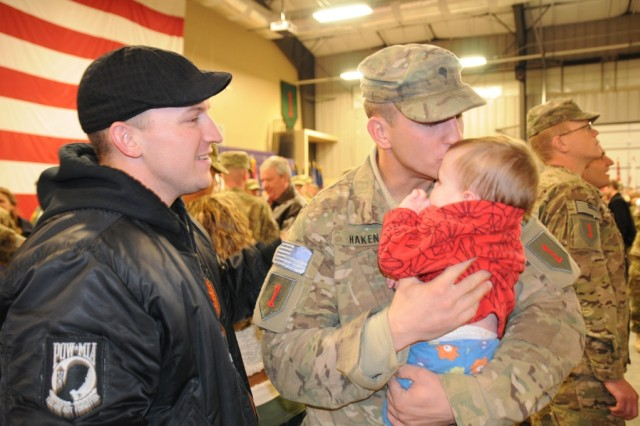 Spc. Hans Haken, an infantryman from Manchester, N.H., assigned to 2nd Battalion, 34th Armor Regiment, 1st Heavy Brigade Combat Team, 1st Infantry Division, embraces his nephew for the first time following a redeployment ceremony at Fort Riley, Kan., Dec. 17. Two more units of the 1st HBCT are expected to return to Fort Riley from Afghanistan before the end of the year.