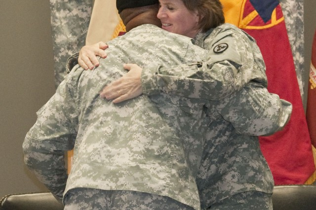 Col. Kristin K. French, commander of the 3d Sustainment Command (Expeditionary), hugs Command Sgt. Maj. Willie C. Tennant Sr. during a change of responsibility ceremony on Dec. 15. During the ceremony, Tennant transferred responsibility to Command Sgt. Maj. Karl A. Roberts Sr.  (U.S. Army photo by Staff Sgt. Michael Behlin)