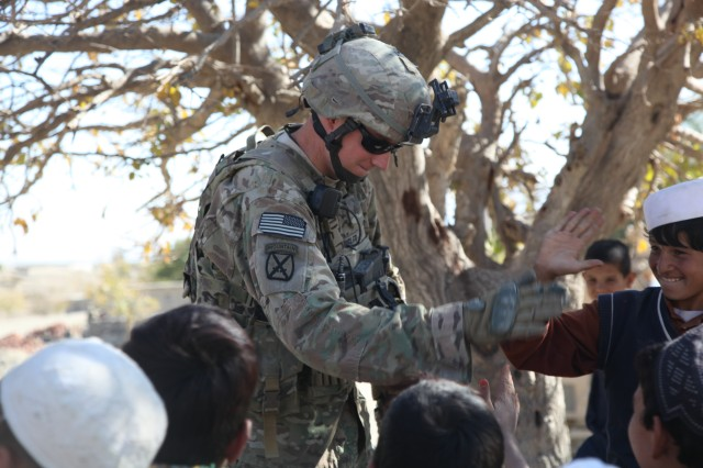 U.S. Army Sgt. Eugene Housler, from Radcliff, Ky., serving with C Troop, 6th Squadron, 4th Calvary Regiment, 3rd Brigade Combat Team, 1st Infantry Division, Task Force Duke, gives high-fives to local Afghan children, Nov. 29, 2011, outside Camp Parsa, Khowst province, Afghanistan. Making themselves a constant presence, U.S. and Afghan forces work to introduce themselves to the locals and discourage insurgent activity.
