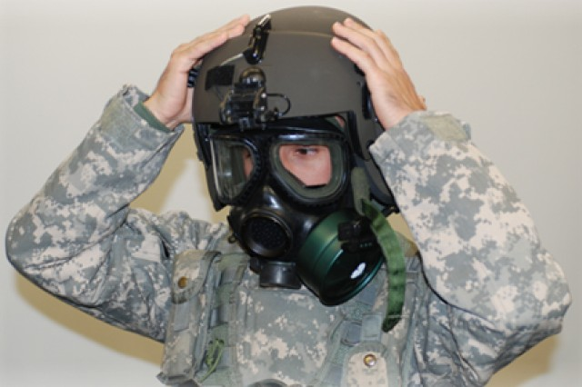 """Spc. Hubert Widener, a UH-60 Black Hawk mechanic from Company B, 602nd Aviation Support Battalion, 2nd Combat Aviation Brigade, stationed at Camp Humphreys, South Korea, puts on the new Joint Protective Aircrew equipment during a """"Train the Trainer"""" course to teach aircrew members how to instruct others on the proper wear of the suit on Oct. 29, 2011."""