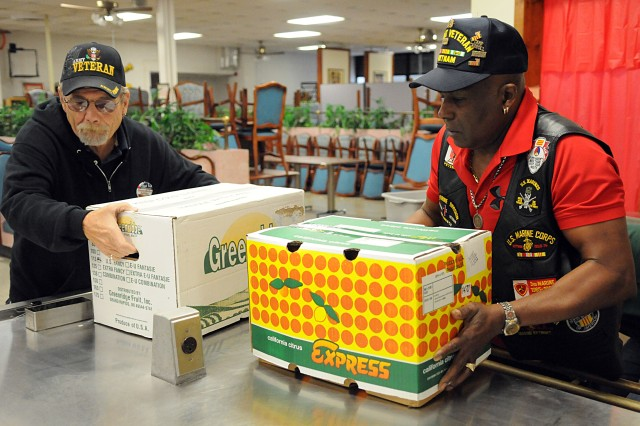Randy Barnett and Tommy Ponds unload boxes of fruit in a Fort Riley dining facility that hosts the USO's weekly No Dough Dinners. The two are members of Vietnam Veterans of America, Heart of America Chapter 317. The chapter is a No Dough sponsor and its members were on post Wednesday, Dec. 14, 2011, to tour Warrior Transition Battalion facilities and help prepare and serve dinner at the dining facility.