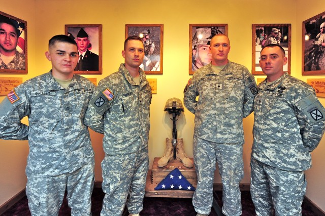 From left, Pfc. Marc Gallant, Spc. Matthew Hagler, Spc. Steven Burtis and Staff Sgt. Carl Chandler, all with 3rd Battalion, 6th Field Artillery Regiment, 1st Brigade Combat Team, 10th Mountain Division (LI), stand in front of the newly dedicated Wall of Heroes in the battalion headquarters honoring the six Centaurs lost in the previous three deployments to Iraq and Afghanistan since 2005.