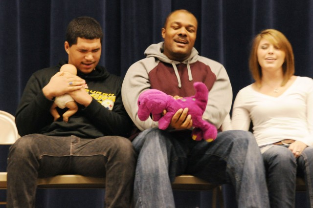 From left, Tristan Chabis, Vannell Berrien and Nina Nowicki, all of whom were in a hypnotic state, believe they are children watching a movie during a stage show Friday at the Multipurpose Auditorium. Fort Drum USO invited Michael Blaine, a hypnotist from Plattsburgh, to visit Fort Drum and entertain Soldiers and Families.