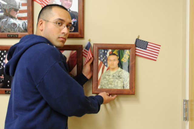 Philip Rivera hangs a photo of his brother, Sgt. Paul Rivera, on the wall of the Hall of Remembrance following the SOS holiday reception at Fort Hood, Texas, Dec. 15, 2011. Philip, who is a Fort Hood Soldier, followed his late brother into the military. He joined his parents and extended family at the reception.