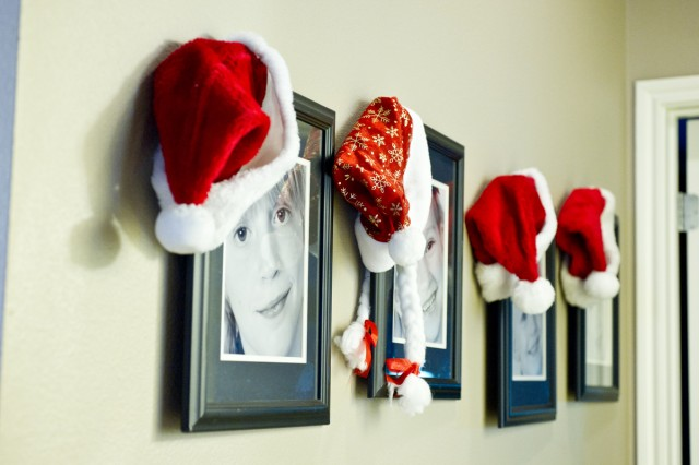 Festive hats hang on photos of the Siegrist children in a hall of the Family's home. Trish said decorations don't need to be expensive to make a fun holiday atmosphere, they just need to capture a Family's sense of fun. (U.S. Army photo by Dawn Pandoliano, III Corps and Fort Hood Public Affairs)