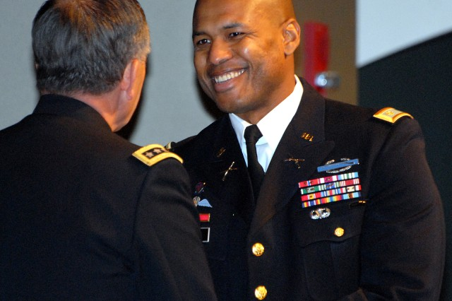 Vice Chief of Staff of the Army Gen. Peter Chiarelli congratulates top U.S. graduate Maj. Anthony Gore, recipient of the Gen. George C. Marshall Award, during the Command and General Staff College graduation for the 2011-02 Intermediate Level Education class Dec. 16 at the Lewis and Clark Center, Fort Leavenworth, Kan. Chiarelli provided remarks at the ceremony.