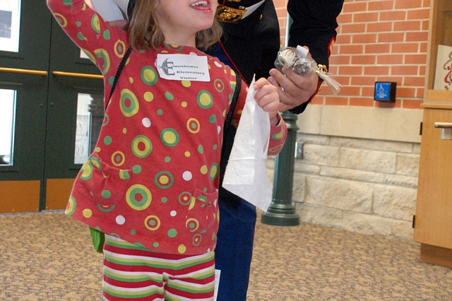 Five-year-old Trina Waugh tries on Staff Sgt. Jose Perdomo's service cap Dec. 16 at Eisenhower Elementary School, Fort Leavenworth, Kan. Perdomo, area Toys for Tots coordinator, was at the school picking up a box of donated toys.