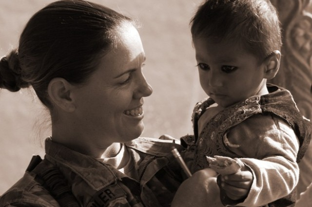 Sgt. Kristin Goehler, female engagement team noncommissioned officer in charge, holds a child during a women's shura in Mohmand Dara District, Afghanistan, Dec. 6, 2011. The female engagement team was comprised of members of the Nangarhar Provincial Reconstruction Team, Agribusiness Development Team and individual district support teams throughout Nangarhar.