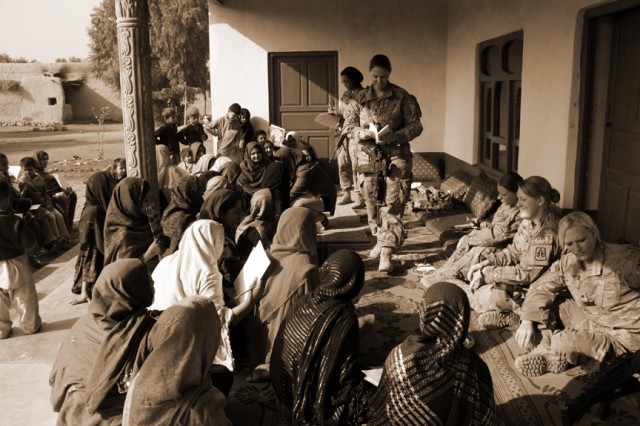 A female engagement team, comprised of members of the Nangarhar Provincial Reconstruction Team, Agribusiness Development Team, and individual district support teams throughout Nangarhar Province, Afghanistan, hand out surveys during an all female shura in Mohmand Dara, Dec. 6, 2011. By surveying women in all the districts of Nangarhar, the female engagement team will identify key women's issues.