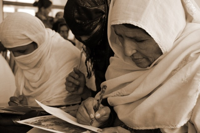 Two local women complete surveys as part of an all-women's shura in Rodat, Afghanistan, Dec. 10, 2011. The multipage survey contains 73 questions addressing an array issues, including education, marriage, violence against women and health care.