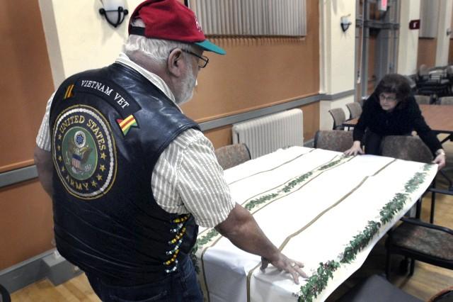 Volunteers Michael Howard, Federal Way, a Vietnam veteran, and Jill Johnson, Bonney Lake, help set up for the VetsMeetVets banquet.