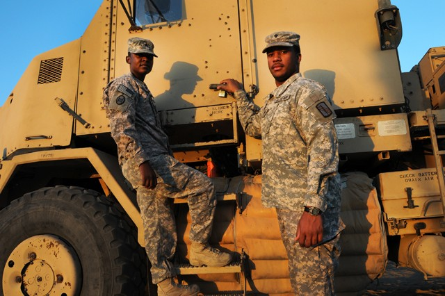 Sgt. Rhondelisha Parker (left) and Spc. Carlos Houston, members of the North Carolina Army National Guard's 1452nd Transportation Company, pose for a team picture next to an M-1070 Heavy Equipment Transporter, much like the one they drove from Iraq to Kuwait during the final convoy here Dec. 18. Both North Carolina natives were excited to be a part of the final convoy, closing the book on the American military presence in Iraq.