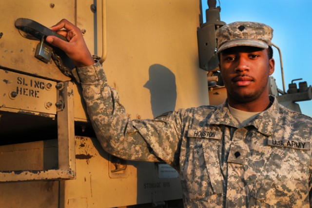 Spc. Carlos Houston, a member of the North Carolina Army National Guard's 1452nd Transportation Company, shows off his M-1070 Heavy Equipment Transporter. The night before, Houston participated in the last convoy out of Iraq.