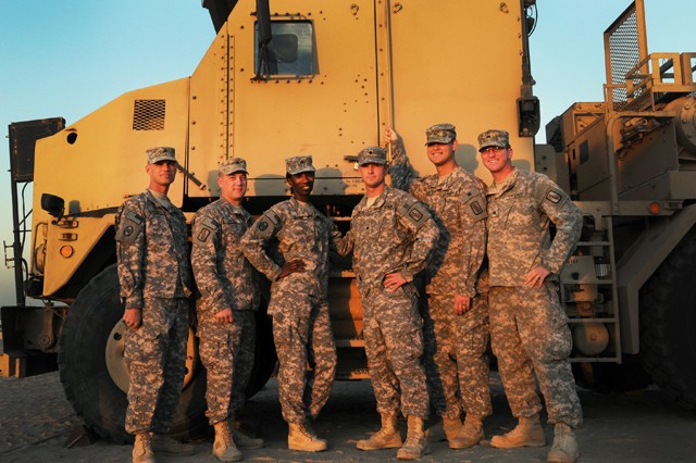 A team of North Carolina Army National Guard Soldiers of the 1452nd Transportation Company here take a group picture in front of an M-1070A1 Heavy Equipment Transporter, Dec. 19, 2011. The night before, this crew were part of a small group of N.C. Guardmembers who participated in the last convoy out of Iraq.