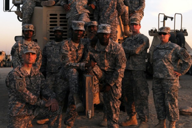 A team of North Carolina Army National Guard Soldiers of the 1452nd Transportation Company take a group picture in front of a Heavy Equipment Transporter, Dec. 19, 2011. The night before, this crew were part of a small group of NC Guardmembers who participated in the last convoy out of Iraq.
