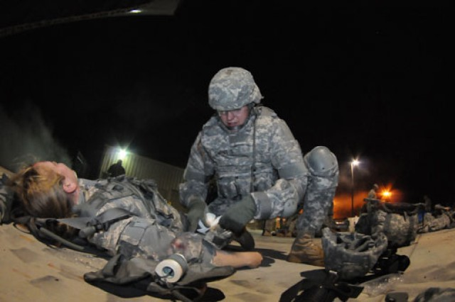 Staff Sgt. Sean Swint, Eighth Army, bandages the arm of a casualty after she was felled by artillery fire at an airfield.