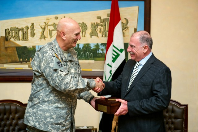 Army Chief of Staff Gen. Raymond T. Odierno, left, presents a gift to Iraqi Council of Representatives Speaker Osama al-Nujaifi during a visit to Baghdad, Dec. 22, 2011.