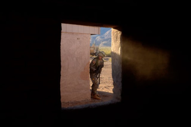 "A Soldier from 1st Squadron, 1st Cavalry Regiment, 2nd Brigade Combat Team, 1st Armored Division, creeps around a corner at a military operations in urban terrain building occupied by suspected ""insurgents."""