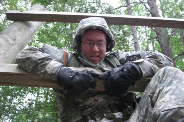 "Brian Ryu, a University of Maryland ROTC cadet, takes on ""The Confidence Climb"" during the obstacle course portion of Operation Indian Summer, a field exercise held at Fort A.P. Hill, Va., in October 2011. The goal of the exercise was to test physical strength and build self-confidence."