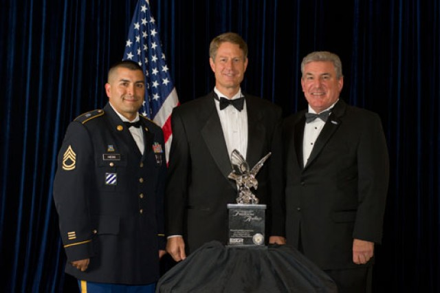 Sgt. 1st Class Leo Hess, a reservist stationed in Afghanistan and firefighter with the Gilbert, Ariz., fire department, along with Gilbert Mayor John Lewis, and David McGinnis, acting assistant secretary of defense for Reserve Affairs, pose with the Freedom Award trophy during a ceremony, Sept. 22, 2011, at the Ronald Reagan Building and International Trade Center in Washington, D.C. The trophy was presented to the town of Gilbert for its support of Guard and Reserve Soldiers. Hess nominated Gilbert for the award as a way of thanking citizens there for supporting his family while he was deployed in support of Operation Enduring Freedom in Afghanistan.