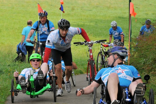 Staff Sgt. Barry Homberg, with the Europe Regional Medical Command's Warrior Transition Battalion, is assisted on an incline during the 18-mile ride around Lake Bostalsee during the Sept. 11 Community Soldier Ride held in Germany. In December of 2006 Homberg was struck by two 7.62 mm rounds in his right calf and hip during a mission in Ramadi, Iraq.