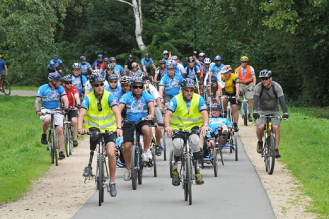 Bilateral amputee and retired Staff Sgt. Dan Nevins, director of Warriors Speak, along with amputee and retired Marine Staff Sgt. Mason Poe, lead a group of participants across the finish line of the 18-mile ride around Lake Bostalsee during the Sept. 11 Community Soldier Ride held in Germany. About 400 participants gathered on the final day of the three-day Soldier Ride to support the wounded warriors and remember the 10th anniversary of the Sept. 11 terrorist attacks.