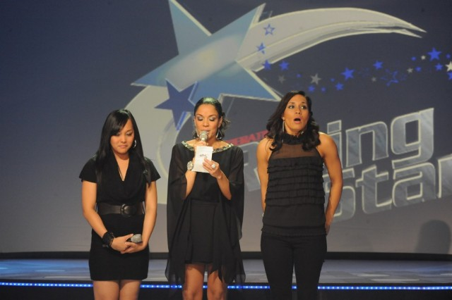 U.S. Army Reserve Sgt. Melissa Neal (right), a former active duty Soldier and current Army wife and mother, reacts as GeNienne Samuels (center) announces Neal as the winner of the 2011 Operation Rising Star singing contest at the Fort Sam Houston Theatre. Runner-up Kristine May Hills of Camp Humphreys, South Korea, stands at left.