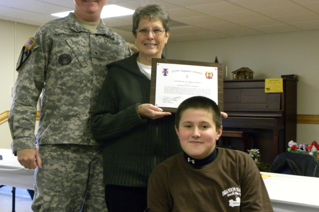 412th Theater Engineer Command deputy commander Brig. Gen. Douglas R. Satterfield commended Carol Schaeffer, owner of Schaeffer's Harley Davidson, for her joint efforts with HHC to raise funds for the Muscular Dystrophy Association, benefiting affected children like Brandon Harris Dec. 11, 2011, Schuylkill Haven, Pa. (Photo: 2nd Lt. Renee Zimmerman)