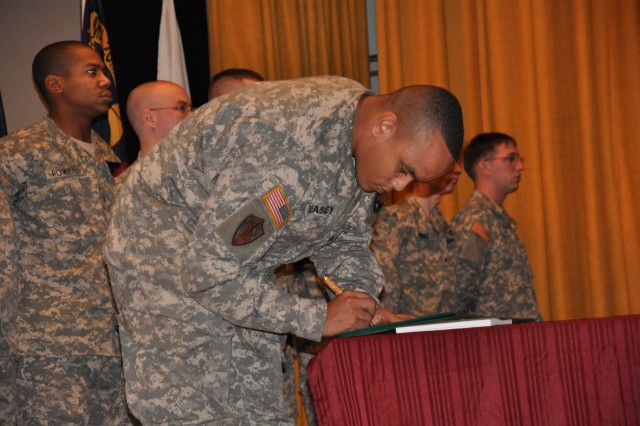 Sgt. Vyncent Beasely signs his name accepting the duties of the noncommissioned officer.