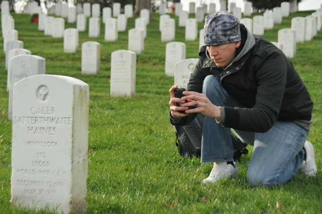 Pvt. Eric Heim, an infantryman with Delta Company, 1st Battalion, 3d U.S. Infantry Regiment (The Old Guard), kneels to photograph the front and rear of a tombstone in Arlington National Cemetery, Va., Dec. 15, 2011. Heim is a part of a task force that photographed and documented more than 259,000 tombstones, grave markers and cremation sites to establish accountability of all remains in the cemetery.