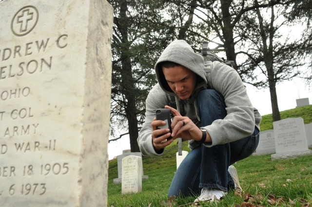 Pfc. Brent Benbow, an infantryman with Delta Company, 1st Battalion, 3d U.S. Infantry Regiment (The Old Guard), kneels in front of a gravestone to photograph the front and rear of a tombstone in Arlington National Cemetery, Va., Dec. 15, 2011. Benbow is a part of Task Force Christman, after Pvt. William Christman, who was the first Soldier buried in the cemetery. Task Force Christman's mission is to photograph and document every tombstone, grave marker and cremation site in the cemetery. The detailed information will go into a large electronic database.