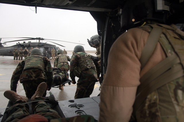 BALKH PROVINCE, Afghanistan - Members of the Afghan National Army, 5th Commando Kandak, unload a casualty from a Black Hawk helicopter during a medical evacuation exercise, Camp Marmal, Afghanistan, Dec. 27, 2011. Afghan commandos trained alongside members of the 1st Cavalry Combat Aviation Brigade to simulate real-life MEDEVAC scenarios for increased combat readiness.