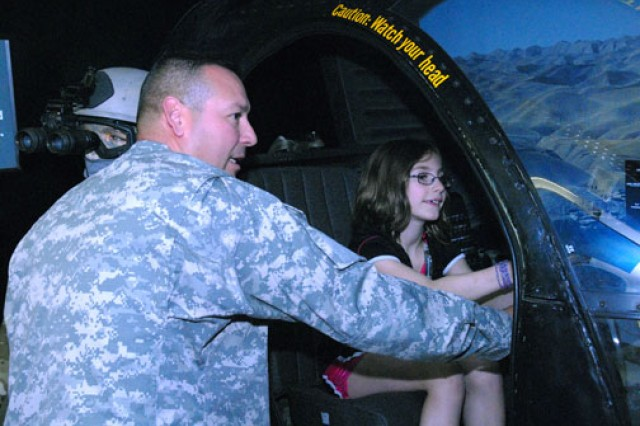 Sgt. 1st Class Abel Garza guides a young visitor through the helicopter simulation.