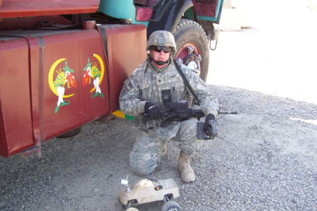 Staff Sgt. Chris Fessenden poses with the remote-controlled truck outfitted with a wireless camera that his brother, Ernest Fessenden, sent to help with vehicle inspections in Iraq. When the staff sergeant went to Afghanistan, he loaned the truck to another patrol. The truck detonated a roadside bomb, potentially saving six lives.
