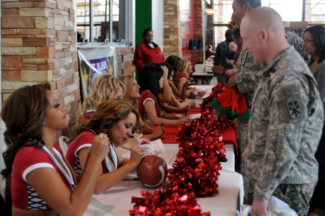 Members of the Arizona Cardinals cheerleading team sign autographs for Soldiers and their families at Freedom Crossing Dec. 15.