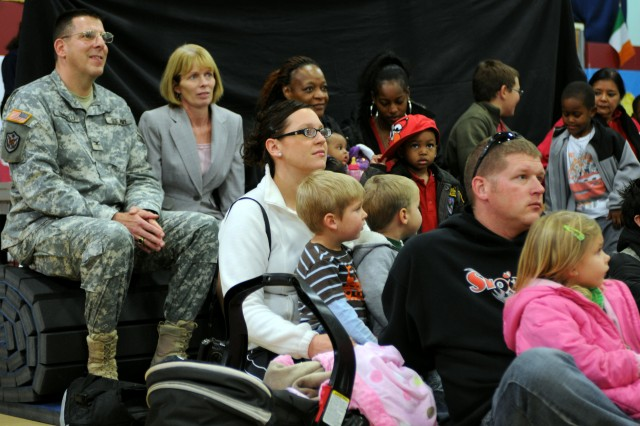 "Col. Joseph A. Simonelli Jr., Fort Bliss garrison commander, watches as Elmo and Rosita, Muppets from Sesame Street, performs for military families at Logan School Age Services Dec. 16. Sesame Street was on Fort Bliss to inform families of its ""Talk, Listen, Connect"" program, which helps military families and their children deal with issues that may be difficult to communicate about."