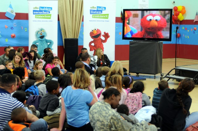 "Military families watch as ""Elmo,"" a Muppet from Sesame Street, learns that his father will be leaving for some time at Logan School Age Services Dec. 16. Sesame Street was on Fort Bliss to inform families of its ""Talk, Listen, Connect"" program, which helps military families and their children deal with issues that may be difficult to communicate about."