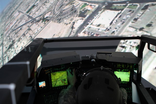"Lt. Col. Edward Vedder ""flies"" an AH-64D Apache Block III helicopter in a flight simulator at Boeing's facility in Mesa, Ariz."