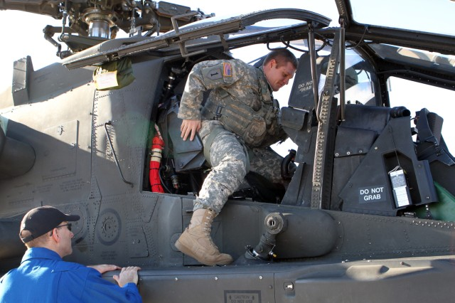 Chief Warrant Officer 2 Shawn Witt climbs into a new AH-64D Apache Block III helicopter for a flight from Boeing's facility in Mesa, Ariz., as Boeing test pilot Bill Lee looks on.