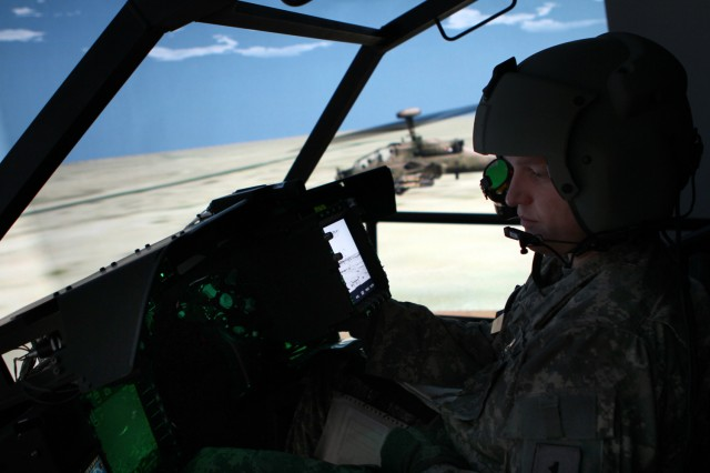 "Chief Warrant Officer 2 Shawn Witt ""flies"" an AH-64D Apache Block III helicopter in a flight simulator at Boeing's facility in Mesa, Ariz."