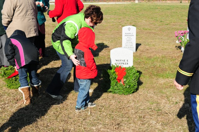 Gold Star Families and members of the local community participate in laying holiday wreaths on 132 gravesites at the Missouri State Veterans Cemetery at Fort Leonard Wood.