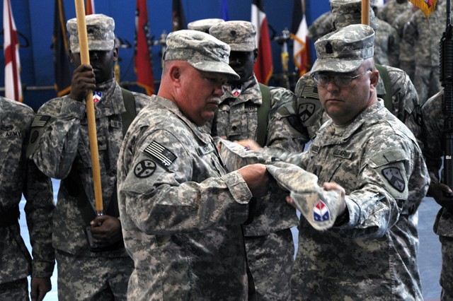 Col. Mark Hart, commander of the Tennessee Army National Guard's 230th Sustainment Brigade, holds his unit's colors still as Command Sgt. Maj. Stanley Massengale, the 230th command sergeant major, pulls the cover over the flag. The 230th SB cased its colors during the transfer of authority ceremony at Camp Arifjan, Kuwait, Dec. 27, 2011, before the North Carolina Army National Guard's 113th Sustainment Brigade unfurled its colors.