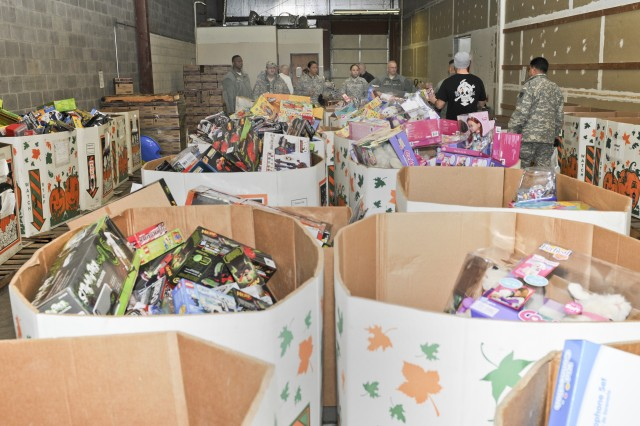 Army Reserve Soldiers prepare to tackle a heap of donated toys for Marine Corps Reserve Toys for Tots program on Dec. 8. (Photo by Sgt. 1st Class Sean Riley, ASC Public Affairs)