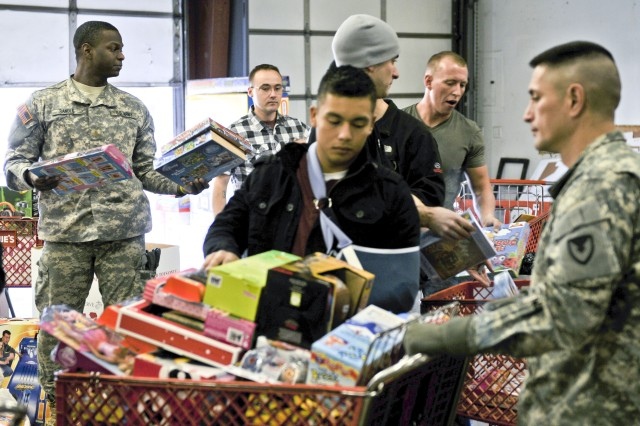 Army Reserve 2nd Lt. Kenneth Randle, far left, passes some donated toys to Marine Corps Reservists for organizing into shopping carts Dec. 8 during the USMC Reserve's annual Toys for Tots campaign.  The donated toys were distributed to Quad Cities families and children. (Photo by Sgt. 1st Class Sean Riley, ASC Public Affairs)
