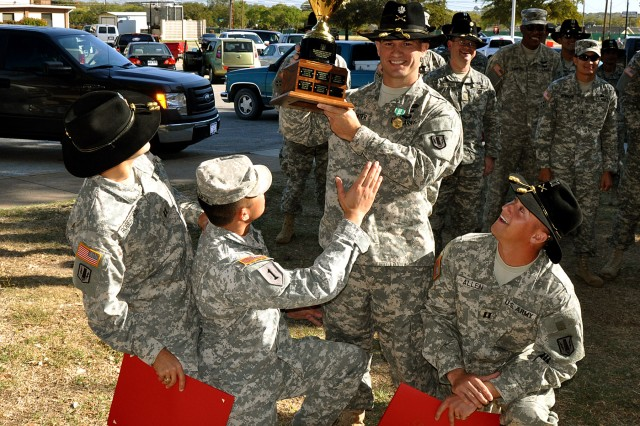 FORT HOOD, Texas--The commanders from the combined team of the Headquarters and Headquarters Battery of the 41st Fires Bde, the 324th Network Support Company, and Battery A, 26th Field Artillery Regiment (Target Acquisition Battery) holds up the trophy after winning the Rail Gunners Army physical fitness challenge on Fort Hood, Texas, Nov.2.